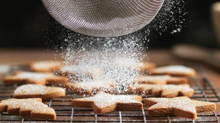 Spolverare con lo zucchero a velo i biscottini di Natale dalla forma a stella e alberelli