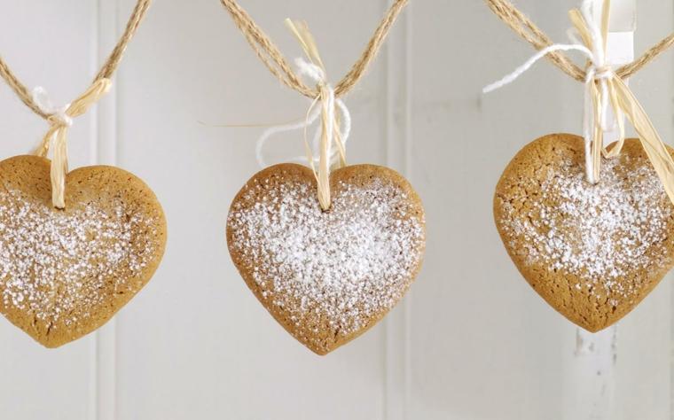 Dolci per Natale, biscotti dalla forma di un cuore con spolverata di zucchero a velo e buchini con filo di canapa per essere attaccati