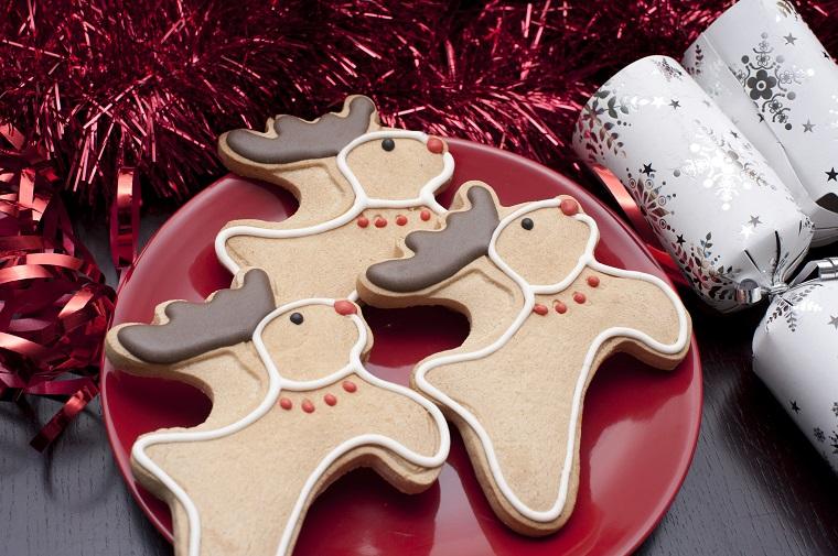 Dolci natalizi, biscotti forma renne di Babbo Natale decorare con cioccolato e glassa reale bianca