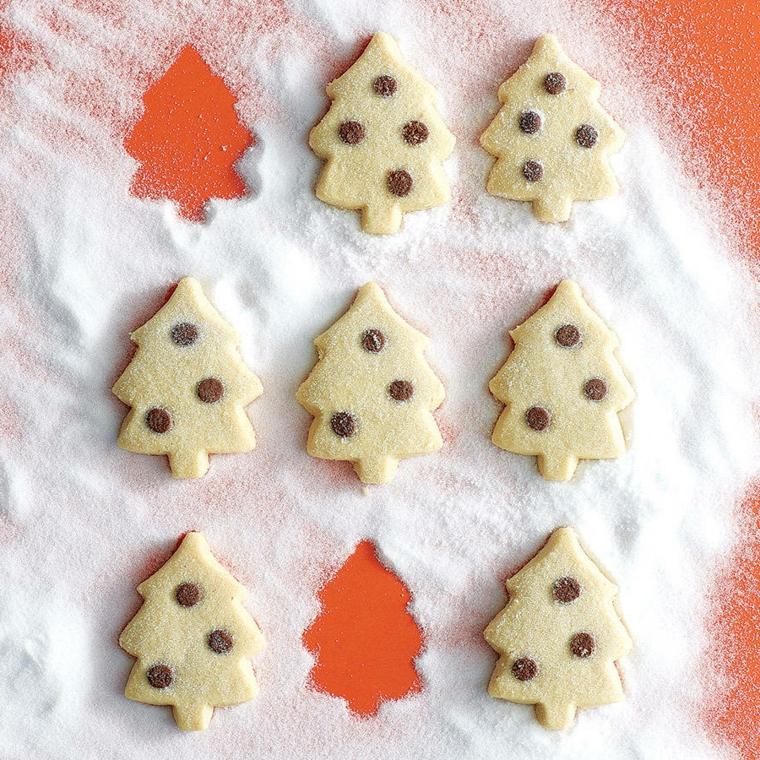 Ricetta facile per fare dei biscotti dalla forma di un albero di Natale e decorati con dei pezzettini di cioccolato