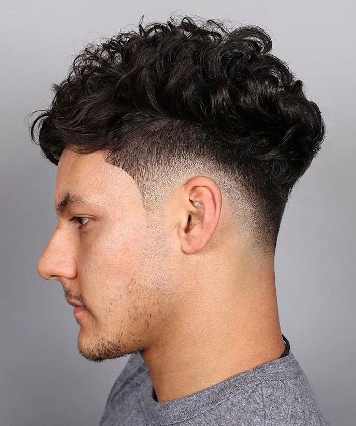 capelli-uomo-sfumati-castano-scuri-ondulati-rasatura-sopra-tempia-lieve-barba-maglione-grigio