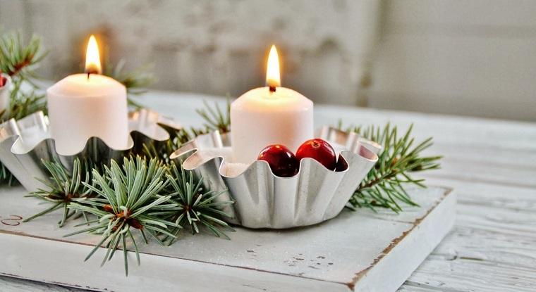 Composizioni natalizie, centrotavola con rametti e portacandele di colore oro decorati con bacche rosse