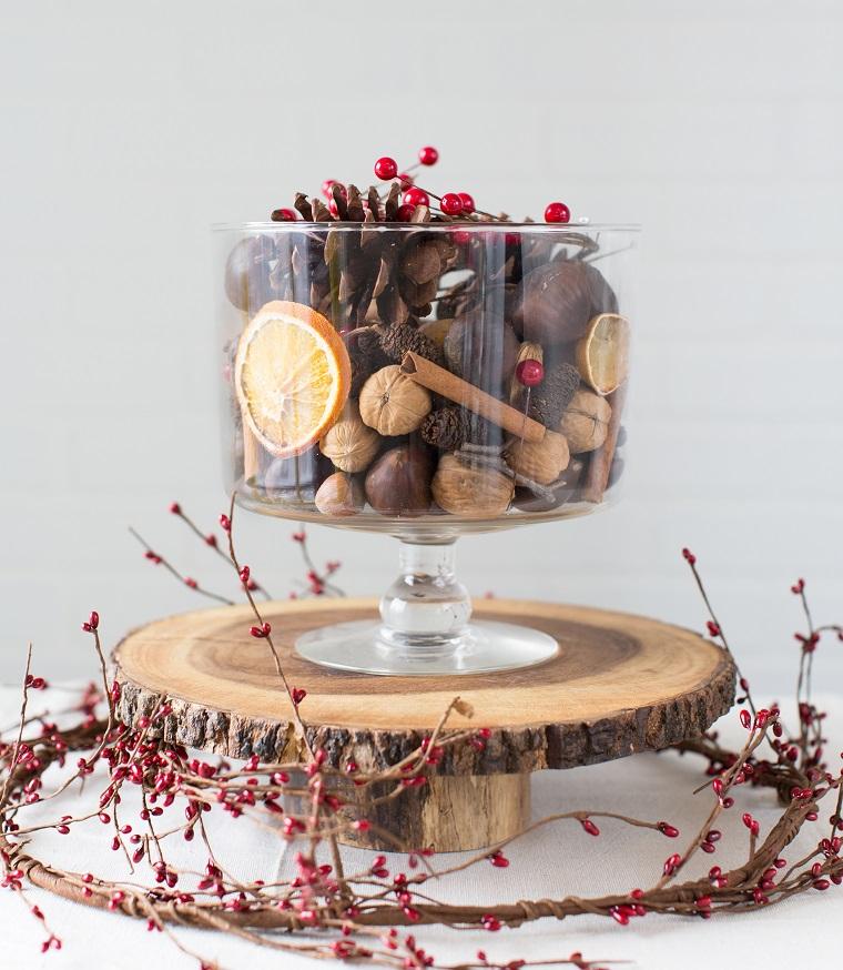 Composizioni natalizie, base di legno e bacche rosse, calice grande di vetro pieno di noci, pigne e bacche rosse