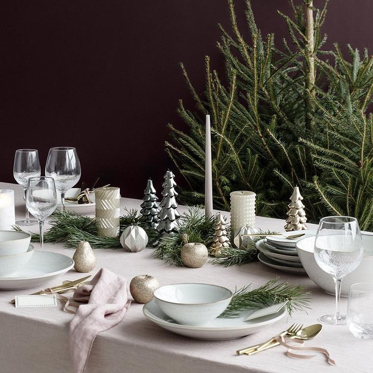 Tavola di Natale, candele a forma di albero di natale colore argento, decorazioni con rametti e palline di natale