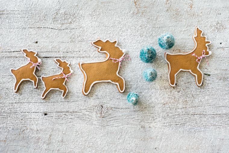 Decorare le renne di Babbo Natale con della glassa reale di colore bianco e cordicine rosso bianche