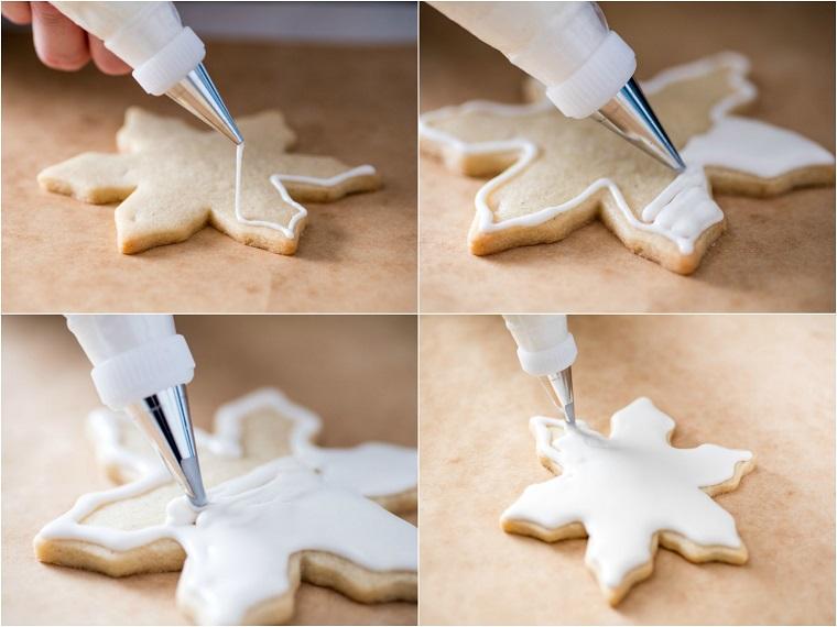Biscotti di Natale, forma fiocco di neve e decorazione con della glassa reale bianca in una sac à poche