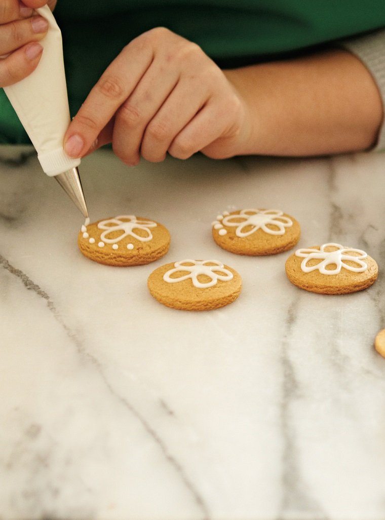 Dolci per Natale, biscotti dalla forma rotonda e decorati con della glassa bianca in una sac à poche