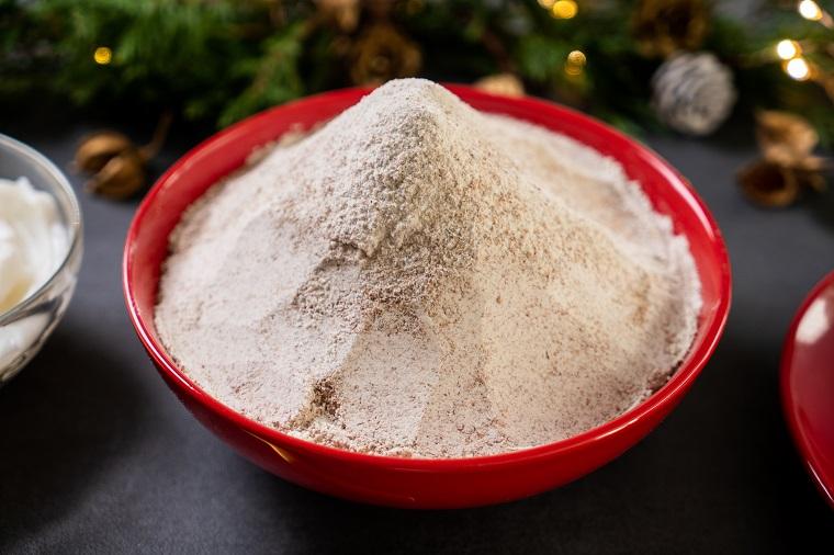 Ricetta biscotti natalizi, ingredienti per preparare i biscotti, ciotola con farina integrale