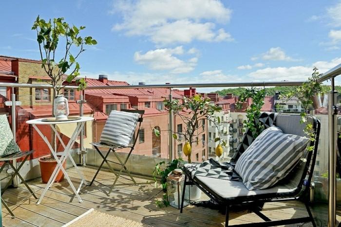 come-arredare-un-balcone-ringhiera-vetro-mobili-legno-colore-bianco-pighevoli-piante-albero-limone-cuscineria