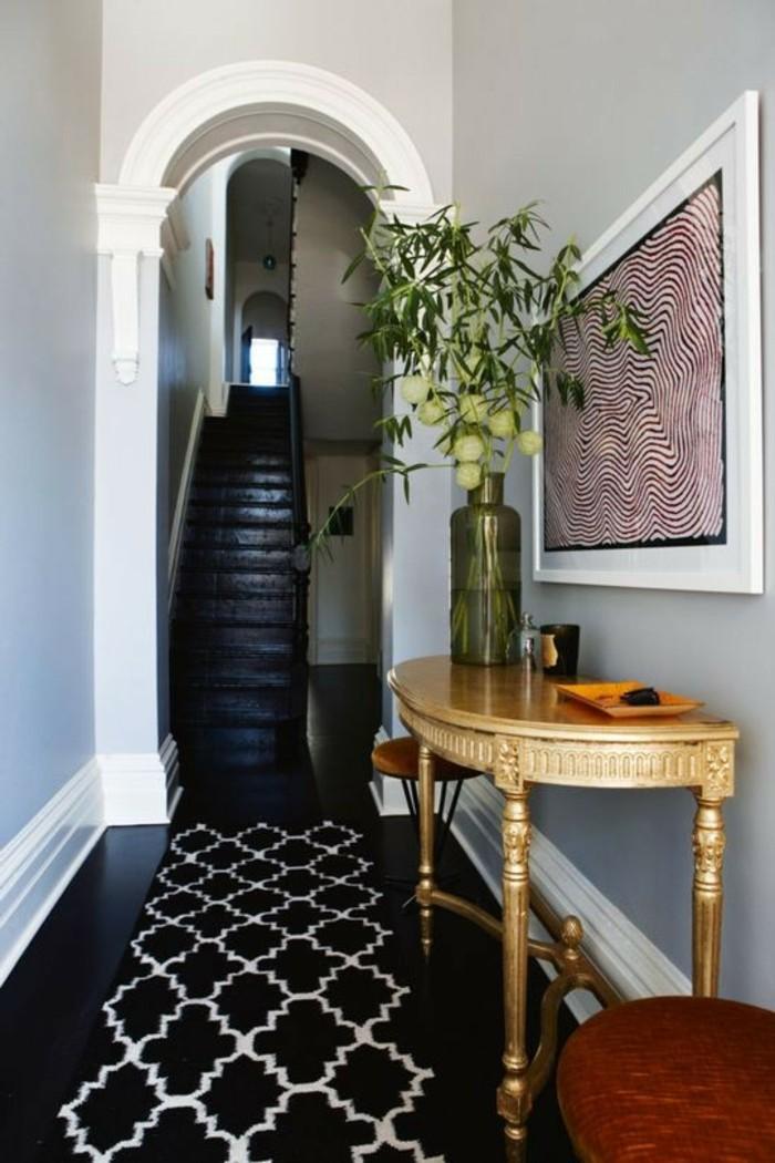 come-arredare-un-corridoio-pavimento-legno-nero-tappeto-tavolino-legno-vaso-fiori-quadro-parete-scale