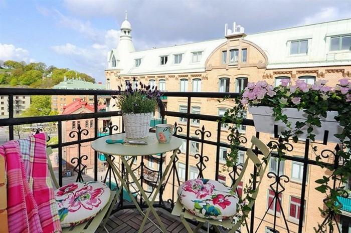 come-arredare-un-terrazzo-mobili-da-esterno-set-ferro-battuto-colore-verde-cuscini-piante-ringhiera
