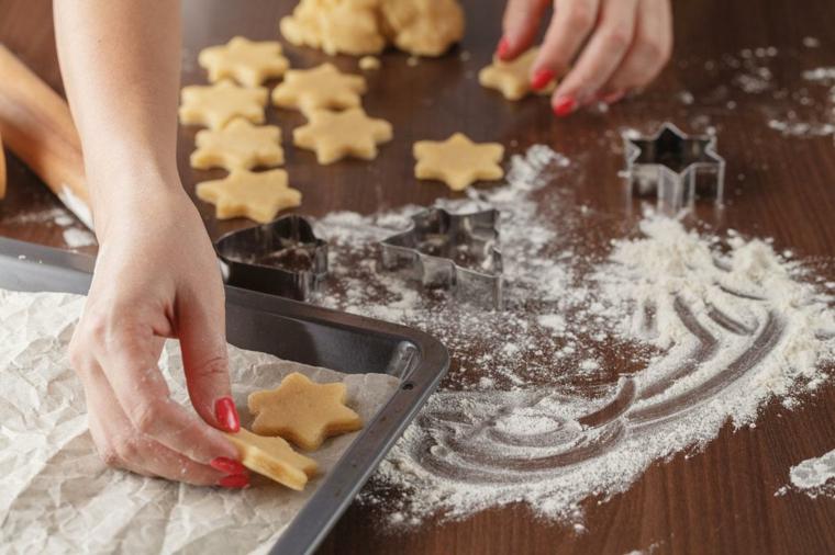 Ricette semplici per biscotti di Natale a forma di stelle, posare su della carta da forno e decorare con zucchero a velo