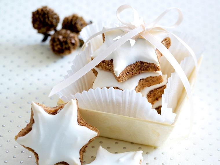Confezione regalo con dei biscotti stella con decorazione di pasta di zucchero di colore bianco