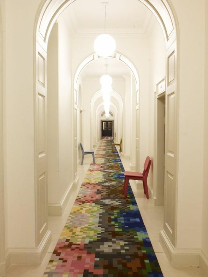corridoio-stretto-lungo-pavimento-tappeto-colorato-sedie-plastica-porte-soffitto-arca-lampadari-sospensione
