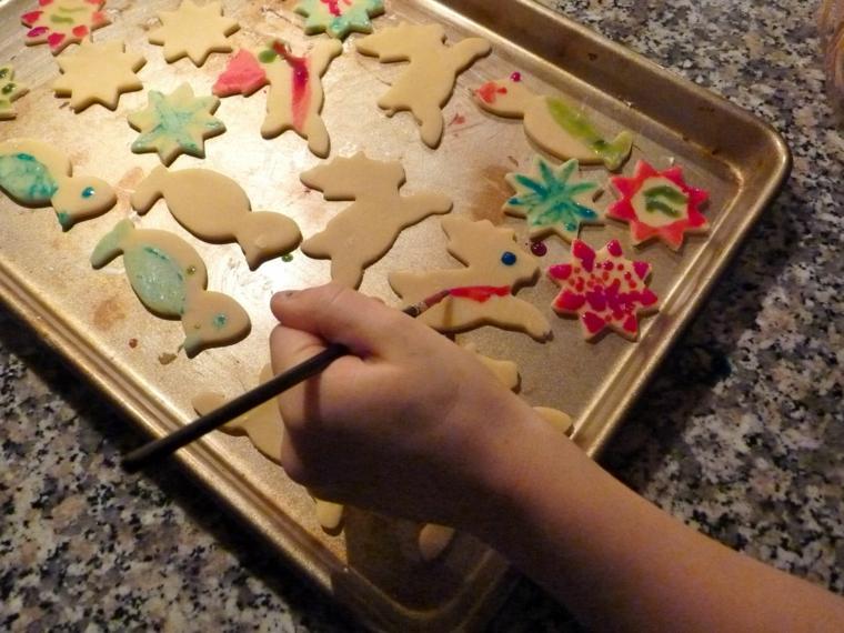 Dipingere i biscotti di Natale dai bambini con pennello e colori alimentari