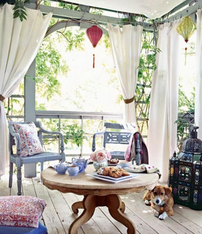 decorazione-balcone-stile-bohèmien-tavolino-basso-rotondo-legno-sedie-tende-veranda-pergolato