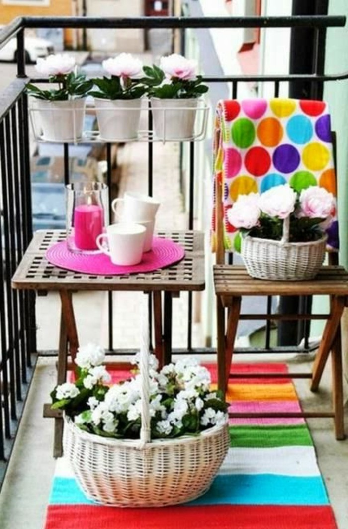 decorazioni-balcone-colorate-cesto-vimini-fiori-piantine-ringhiera-tavolino-legno-sedia-pieghevole-tappeto-colorato