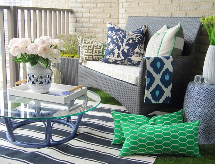 decorazioni-da-esterno-balcone-piccolo-decorato-tappeto-tavolino-rotondo-vetro-vaso-fiori-divano-rattan-cuscini-verdi-ringhiera