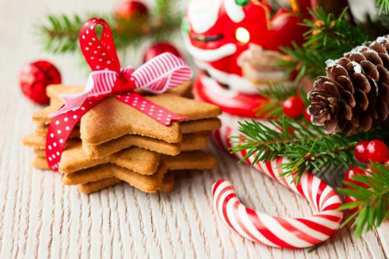 Confezione di biscotti come regalo natalizio, decorati con nastro rosso a pois e bastoncino di zucchero