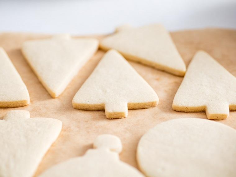 Biscotti natalizi, forma ad albero di Natale con impasto al burro stesi su carta da forno