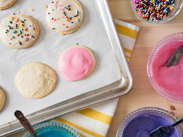 Ricette di Natale, biscotti dalla forma rotonda decorati con della glassa reale di colore rosa
