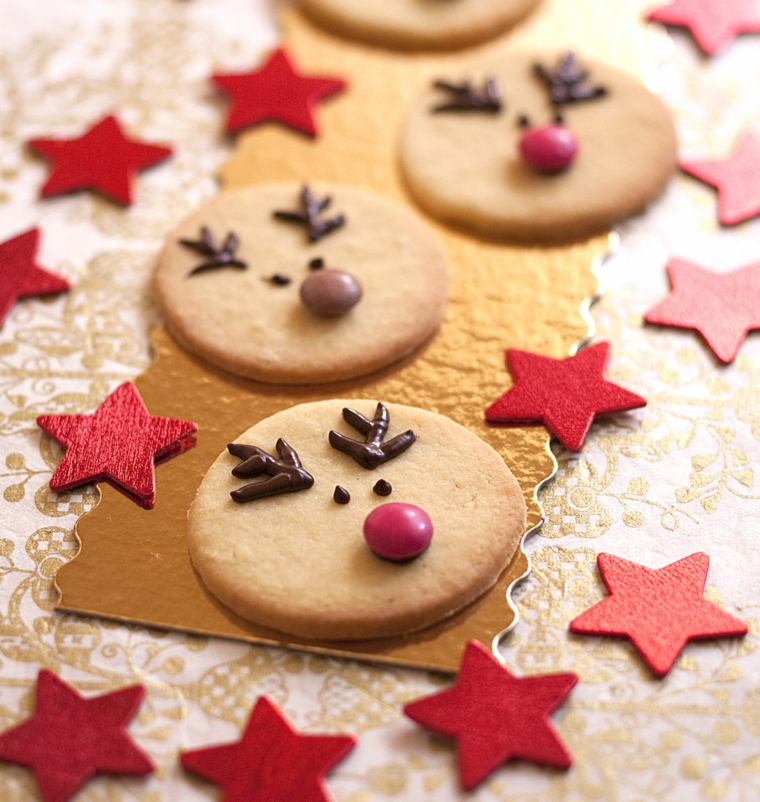 Preparare dei biscotti dalla forma rotonda e decorali con caramelle e cioccolato per assomigliare a delle renne