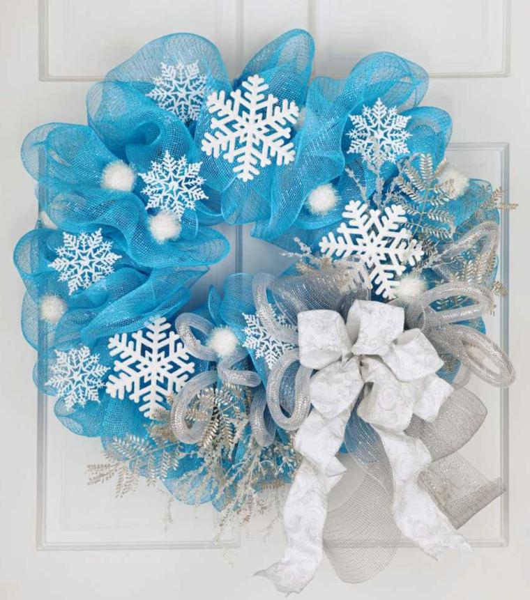 ghirlanda natalizia creata con del nastro arricciato azzurro e grigio, fiocchi di neve e palline bianche