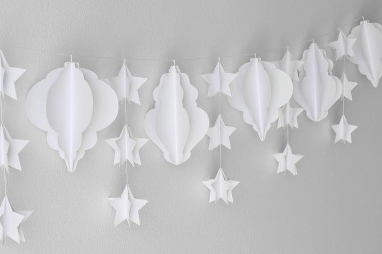 ghirlanda natalizia, una proposta tutta in bianco con delle stelle e degli elementi decorativi appesi ad un filo