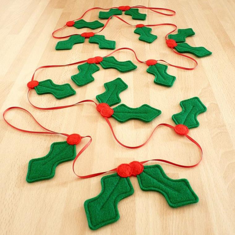 ghirlanda natalizia creata con del feltro a forma di foglie e bacche rosse attaccate a un nastro rosso