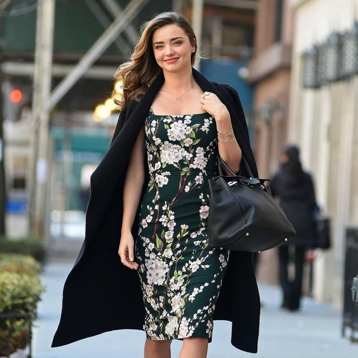 idea-come-vestirsi-bene-ragazza-giovane-capelli-castani-abbigliamento-elegante-vestito-verde-motivi-floreali-cappotto-nero-lungo-borsa-mano