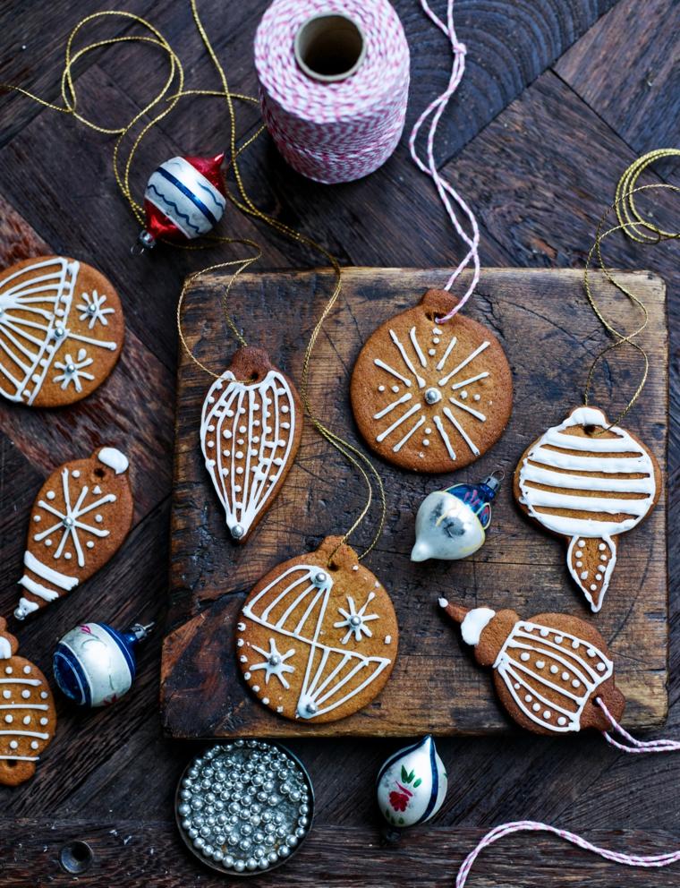 Biscotti da appendere con del nastro, forma rotonda e decorati con della glassa bianca