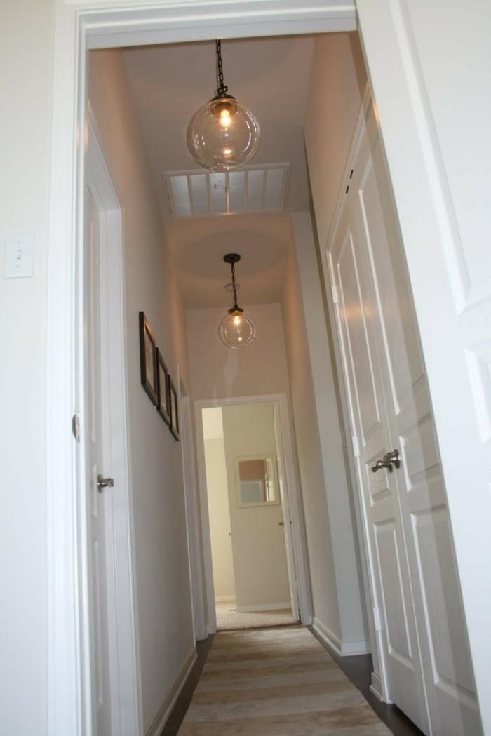 illuminazione-corridoio-stretto-lungo-pavimento-parquet-tappeto-lampade-soffitto-decorazione-pareti-quadri