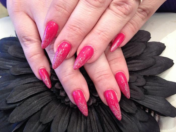 immagini-di-unghie-colorate-base-fucsia-glitter-degradè-fiore-petali-neri-forma-unghia-stiletto