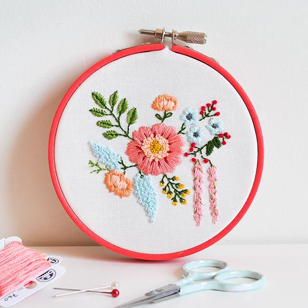 imparare-a-ricamare-cerchio-rosso-ricamo-telo-disegno-motivi-floreali-filo-forbice-ago-punta-rotonda-idea-hobby