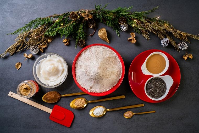 Ingredienti in ciotole rotonde, biscotti di Natale, rametti verdi con pigne e foglie secche