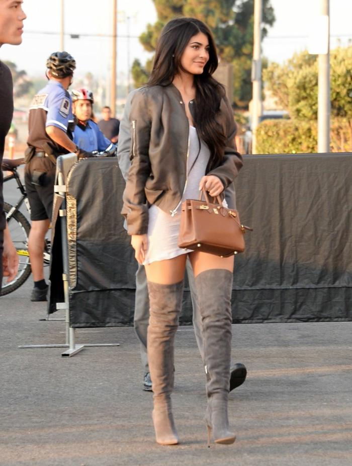 kylie-jenner-ragazza-giovane-vestito-corto-stivali-molto-alti-giacca-abbinata-borsetta-marrone-capelli-lunghi