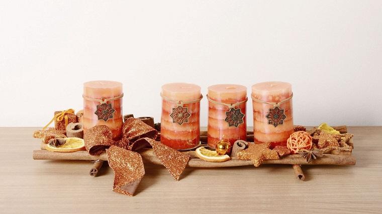 Centrotavola natalizi, idea con una base di legno, candele profumate alla cannella, decorazione con pezzettini di limone e nastro fiocco