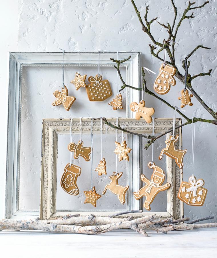 Appendere i biscotti natalizi sui rametti di un alberello e decorali con della glassa reale bianca