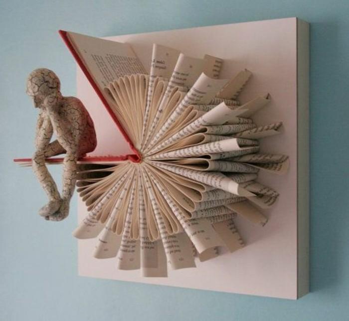 libri-piegati-scultura-appendere-muro-orologio-uomo-pensieroso-appoggiato-copertina