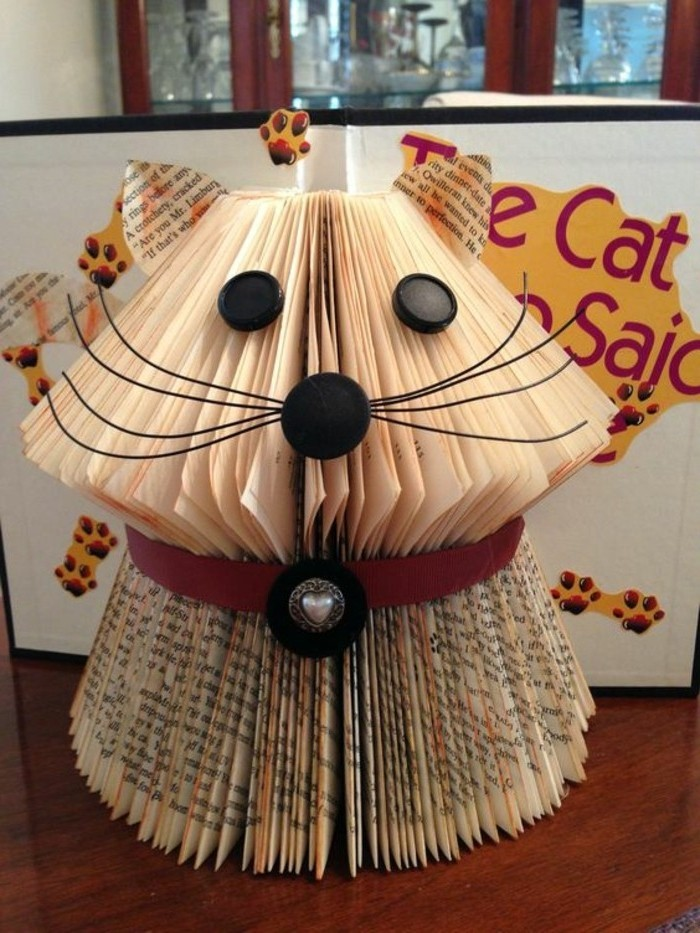 libro-piegato-cane-aspetto-buffo-realizzato-aggiungendo-decorazioni-naso-baffi-occhi-collare