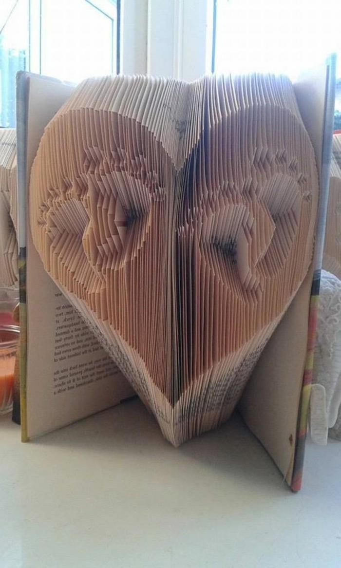 libro-piegato-un-grande-cuore-interno-impronte-due-piedini-realizzato-piegando-pagine-vecchio-libro