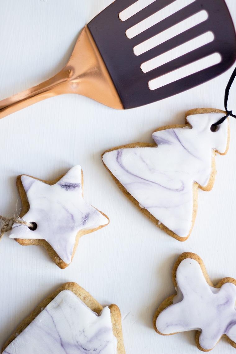 Biscotti decorato con della pasta di zucchero di colore bianco e dalla forma natalizia con stelle e albrelli di Natale