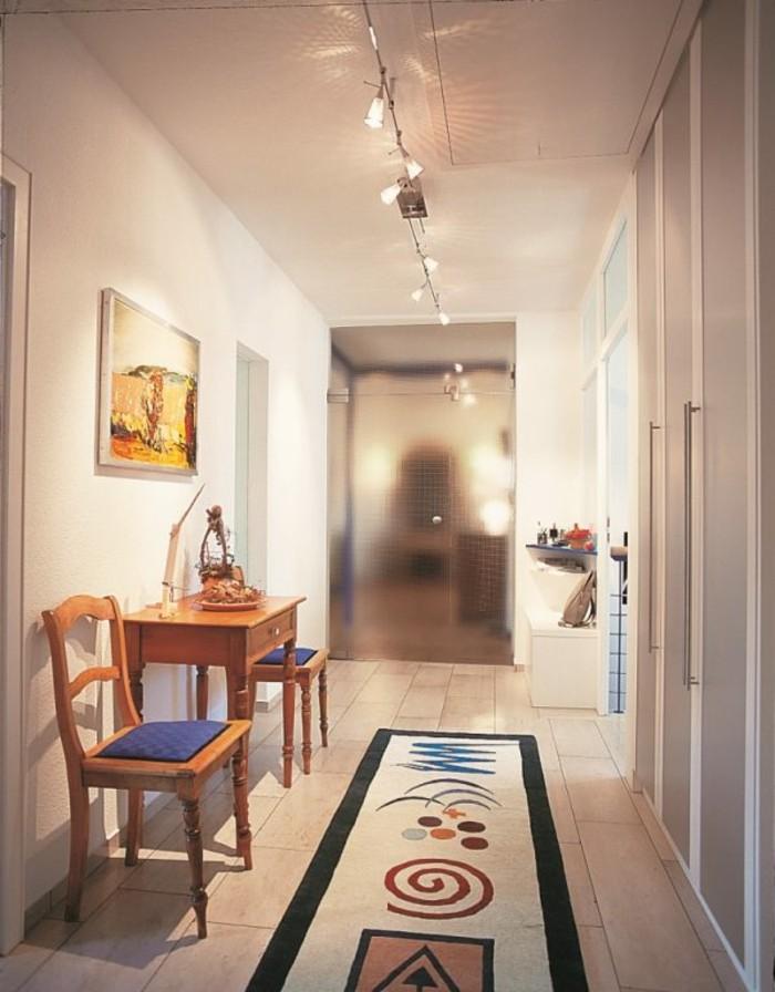 mobili-per-corridoio-tavolino-legno-sedie-tappeto-colorato-illuminazione-moderna-soffitto