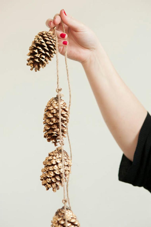 idea per decorare la casa per le feste, una ghirlanda creata con delle pigne dorate