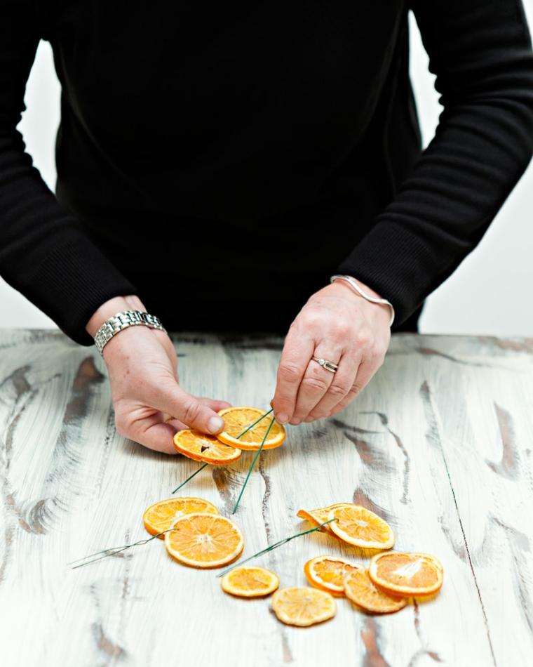 con delle fette di arance essiccate è possibile creare degli addobbi di natale creativi
