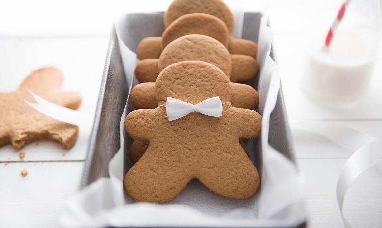 Confezione regalo di biscotti natalizi dalla forma di omini di pan di zenzero con fiocco