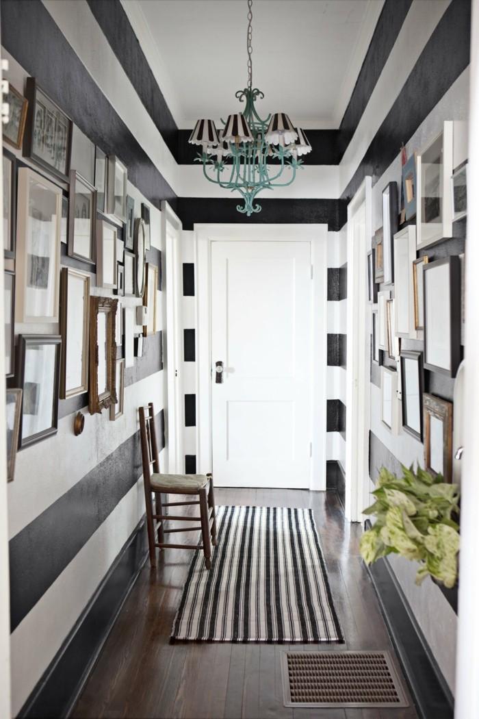 pareti-decorate-contrasto-bianco-nero-lampadario-sospensione-quadri-tappeto-sedia-legno