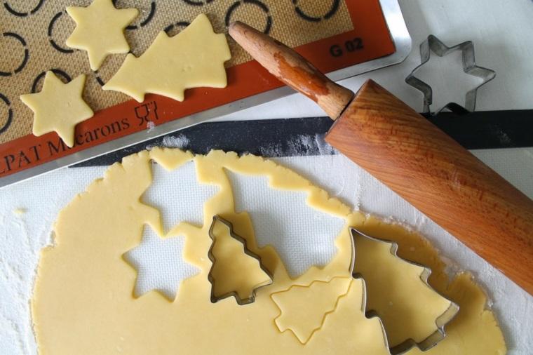 Stampi per biscotti in metallo, impasto e mattarello in legno per lavorarlo