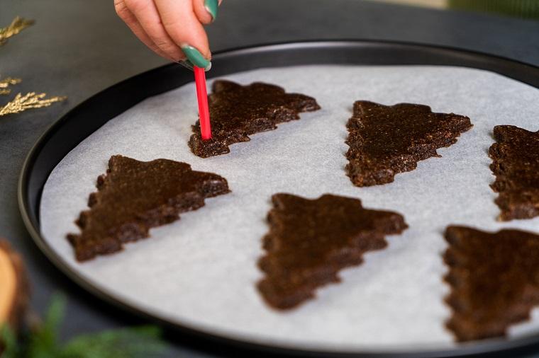 Biscotti a forma di albero di Natale, impasto per biscotti, teglia con carta da forno