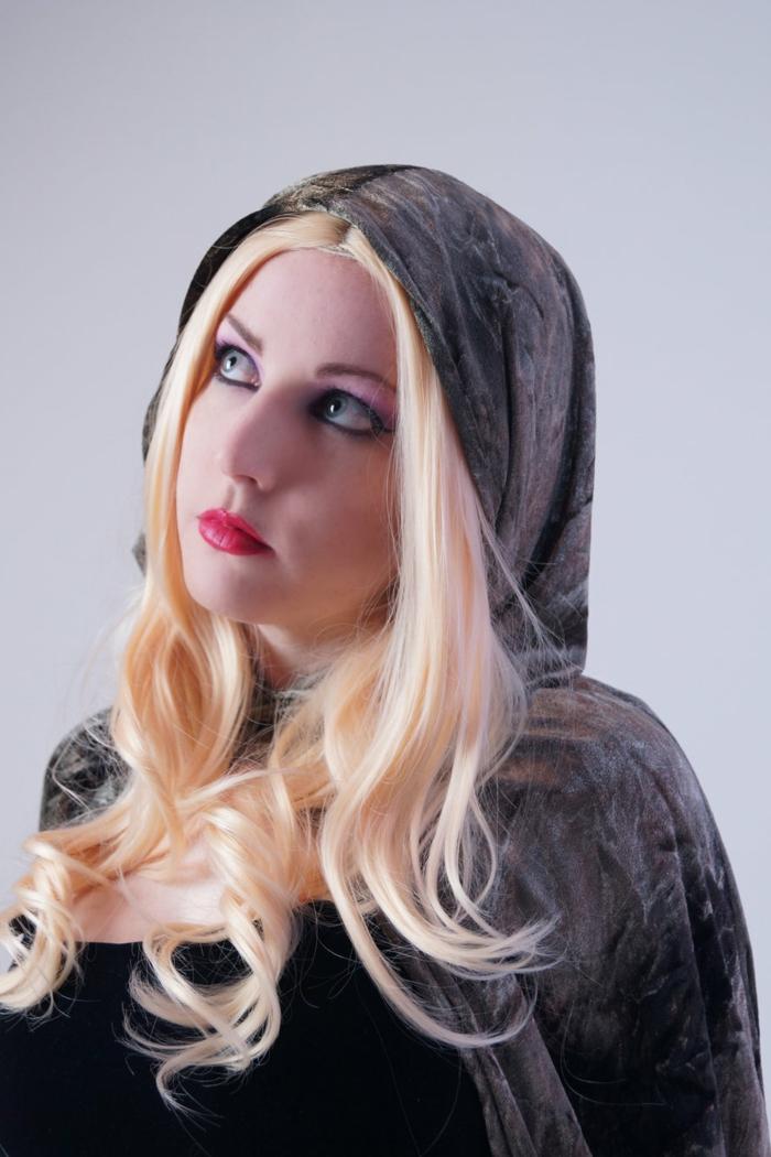 ragazza-capelli-biondo-platino-onde-finali-riga-mezzo-vestito-cappuccio-nero-stile-medievale